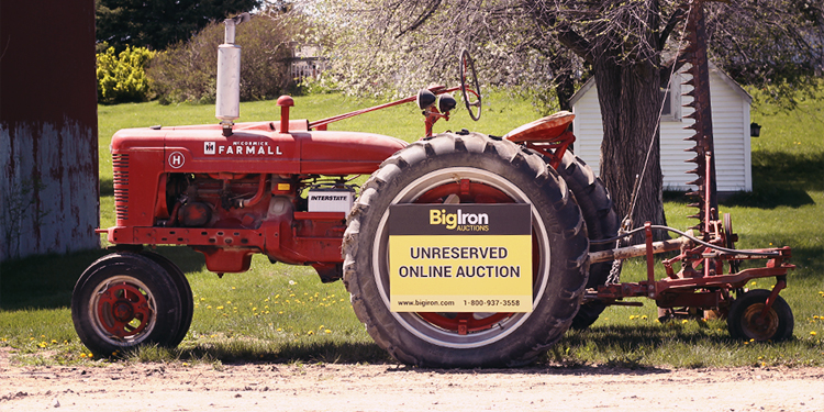 Antique Farmall Tractor with BigIron Online Auction Sign on the Wheel