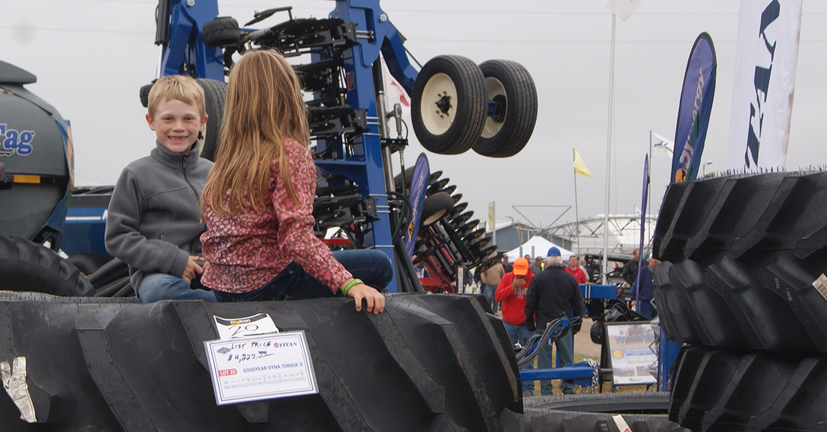 Young boy and girl watch the auction from their seat on top of a stack of tires